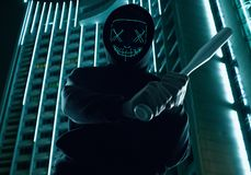 Anonymous criminal man with baseball bat in a black hoodie and neon mask