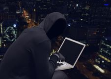 Anonymous Criminal Man in hood on laptop in front of night city. Digital composite of Anonymous Criminal Man in hood on laptop in front of night city Stock Photos