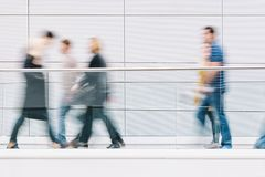 Large crowd of people walking in a clean futuristic corridor. Anonymous crowd of people rushing in a corridor, with copy space. ideal for websites and magazines Royalty Free Stock Photos