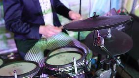 An unrecognizable drummer in a jacket, a man playing drums, a drummer in a music band, a live performance. Anonymous stock video