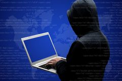 Anonymous faceless hacker in black clothing stands back, works on code on laptop computer, isolated over dark blue interface backg stock photography