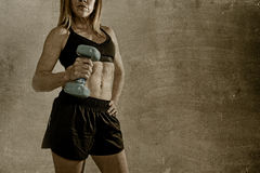 Anonymous fit and strong sport woman holding weight on her hand posing defiant in cool attitude Stock Photo