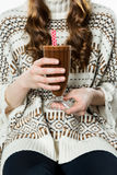 Anonymous girl holding glass of hot chocolate with red straws Royalty Free Stock Images