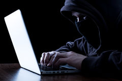Anonymous hacker in the dark. Anonymous hacker with laptop in the dark. Cyber security concept Royalty Free Stock Photo