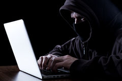 Anonymous hacker in the dark. Anonymous hacker with laptop in the dark. Cyber security concept royalty free stock images