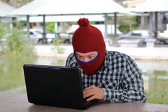 Anonymous hacker hacking steal data with laptop. Royalty Free Stock Image