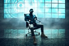 Anonymous hacker sitting in the room Royalty Free Stock Photography
