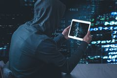 Anonymous hacker with tablet in front of binary code cyber security stock photo