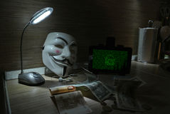 An anonymous hacker tries to crack the operating system`s protection Royalty Free Stock Image
