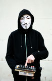 Anonymous hacker. Young anonymous hacker with vintage keyboard Stock Photo