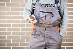 Anonymous handyman with mobile phone, 24/7 help concept Royalty Free Stock Photography