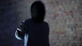 Anonymous hooligan threatening with gun, robbery aggression, armed criminal. Stock footage stock video footage