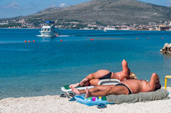 Anonymous, larger bodies sunbathing. Ciovo, Split, Croatia, 29 September, 2014, Editorial, Overweight couple lying on a tourist beach with island in background stock photography