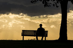 Anonymous male silhouette sitting on a bench at sunset. A lone man sits on a bench during a dark and cloudy sunset Stock Images