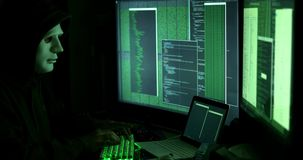 Anonymous man hacking computers in dark room stock video footage