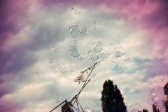 Bubbles and Sky. An anonymous man making giant soap bubbles on an early summer Sunday afternoon at Mauerpark, and a kid trying to catch the bubbles. Image Royalty Free Stock Images