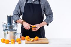 Anonymous man preparing fresh orange juice using electric juicer, healthy lifestyle detox concept on white background. Royalty Free Stock Images