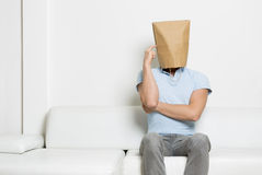 Anonymous man sitting on sofa and thinking. Inquiring anonymous man with head covered by a blank paper bag sitting on sofa with finger at temple, while thinking Stock Image