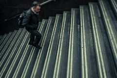 Anonymous man walking up stairs stock photo