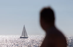 Anonymous man watching a sailboat. An unidentified man on a beach watches a sailboat go by. The image can convey envy, loneliness or (lack of) success Stock Photo