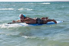 Man in mask posing with board. Anonymous man wearing clown mask and floating with board in ocean water stock photos