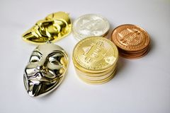 Anonymous mask and bitcoins. Gold and silver anonymous mask and silver, gold and brass bitcoin coins stock image