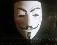 Anonymous mask on computer. Anonymous or V for Vendetta face mask or Guy Fawkes mask from the movie V for Vendetta. Isolated on white background. Concept of Stock Images