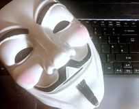 Anonymous mask on computer Royalty Free Stock Photography