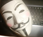 Anonymous mask on computer. Anonymous or V for Vendetta face mask or Guy Fawkes mask from the movie V for Vendetta. Isolated on white background. Concept of Royalty Free Stock Photo