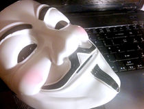 Anonymous mask on computer. Anonymous or V for Vendetta face mask or Guy Fawkes mask from the movie V for Vendetta. Isolated on white background. Concept of stock photography