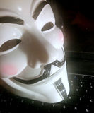 Anonymous mask on computer. Anonymous or V for Vendetta face mask or Guy Fawkes mask from the movie V for Vendetta.  on white background. Concept of hacker group Stock Photos