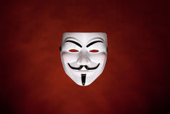 Anonymous mask (Guy Fawkes Mask). Studio shot of an Anonymous face mask, known as Guy Fawkes Mask from the movie V for Vendetta on dark red background royalty free stock photo