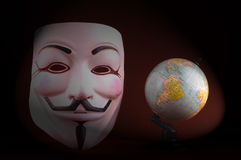 Anonymous mask (Guy Fawkes Mask). Shot of an Anonymous face mask on the red background with globe, known as Guy Fawkes Mask from the movie V for Vendetta Stock Photos