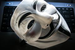 Anonymous mask on keyboard. Anonymous is a decentralized international hacktivist group that is widely known for its various DDOS cyber attacks against several stock images