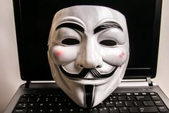 Anonymous mask on keyboard. Anonymous is a decentralized international hacktivist group that is widely known for its various DDOS cyber attacks against several stock photos