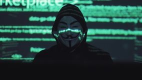 Anonymous in the mask steals user data on the network. hacker against the background of running code. The hacker in the mask hacks the program. the digital stock video footage
