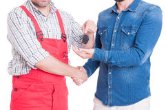 Anonymous mechanic handing car key to customer or client Stock Photos