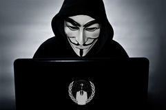 Anonymous member with computer with the vendetta mask. Paris - France - 25 January 2015 - anonymous member with computer with the vendetta mask the symbol of stock photos