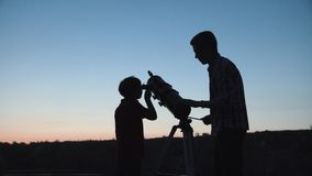 Man and boy using telescope. Anonymous men with little boy looking through telescope in twilight royalty free stock images