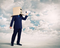 Anonymous message. Businessman wearing carton box on head and speaking in megaphone Royalty Free Stock Photo