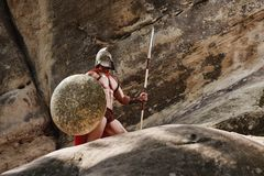 Greek warrior posing on rocks Stock Images
