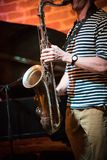 An anonymous musician in a striped t-shirt plays the saxophone in a jazz bar, live performance stock photo