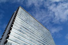 Anonymous office building. Two sides of tall office building against blue sky with light clouds stock photos