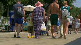 Anonymous pedestrians walking along a busy sidewalk. ANAPA, RUSSIA - JULY 26, 2017: the feet of people walking in the summer along the sidewalk in the resort stock video