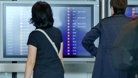 Anonymous people checking flight schedule. Passengers passing by airport arrival departure board stock video