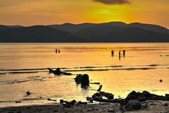 ANONYMOUS PEOPLE FROLICKING SEA SUNSET. Orange dusk sky reflected in the sea with anonymous people frolicking and mountains in background Stock Photo