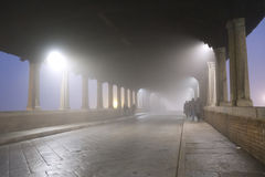 Anonymous people. Anonymous people walking on a covered bridge in a foggy evening stock photography