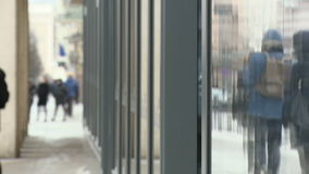 Anonymous people walking in the street of a city with showcase reflections stock video footage