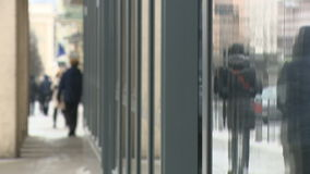 Anonymous people walking in the street of a city with showcase reflections stock footage
