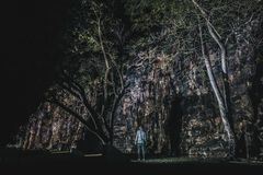 Anonymous person near cave and trees royalty free stock photo